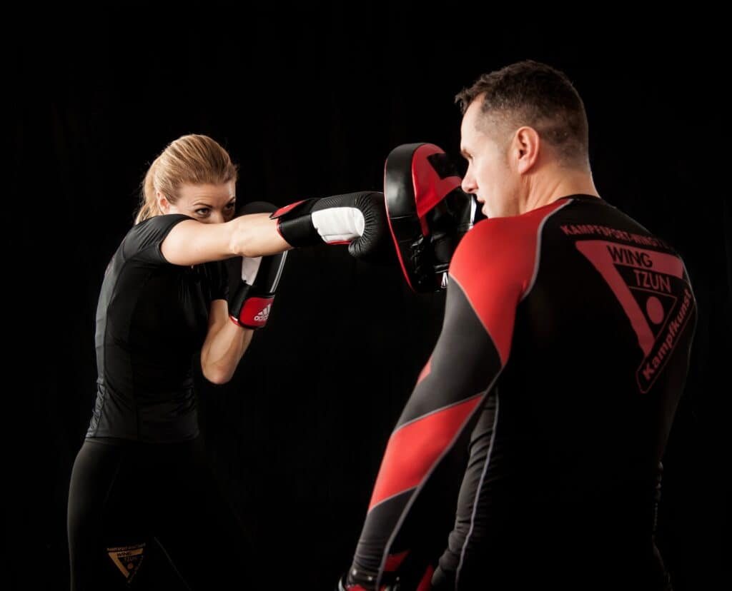 a woman is throwing a punch to her trainer during Krav Maga training for women